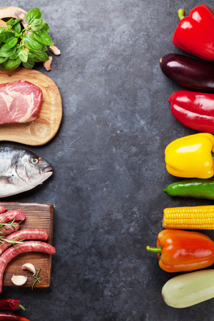 Vegetables, fish, meat and ingredients cooking. Tomatoes, eggplants, corn, beef, eggs, cheese. Top view with copy space on stone table Stock Photo