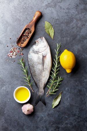 Cuisson de poisson cru et ingrédients. Dorado, citron, herbes et épices. Vue de dessus sur la table en pierre