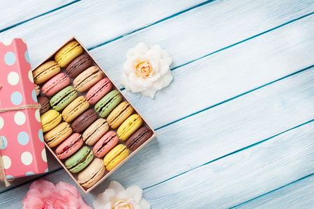 cookies: Colorful macaroons and rose flowers on wooden table. Top view with copy space for your text