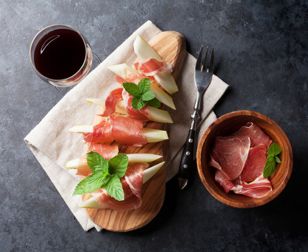 antipasti: Fresh melon with prosciutto and basil. Antipasti and red wine. Top view on dark stone table Stock Photo