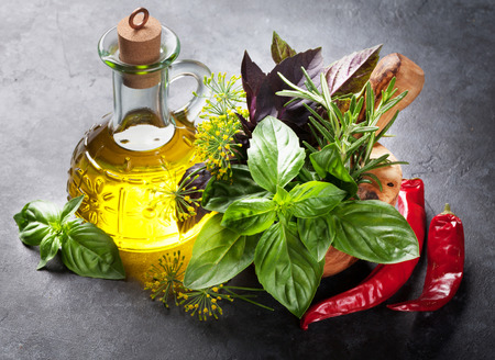 aceite de cocina: Fresh garden herbs in mortar, chili pepper and olive oil on stone table. Basil, rosemary, dill. Cooking ingredients