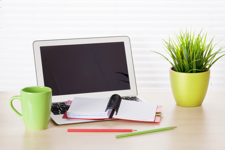 wood blinds: Office workplace with laptop and supplies on wood desk table in front of window with blinds
