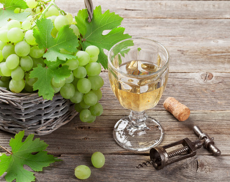 white grape: White grape in basket and glass of wine on wooden table