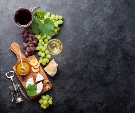 Red and white wine glasses, grape, cheese and honey over stone table. Top view with copy space