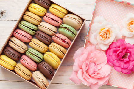 Colorful macaroons and rose flowers on wooden table. Sweet macarons in gift box. Top view Stock Photo