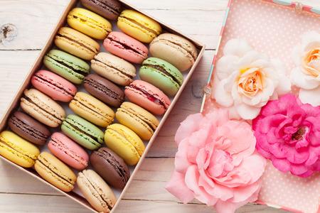 colorido: macarrones de colores y flores color de rosa en la mesa de madera. macarons dulces en caja de regalo. Vista superior