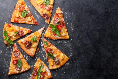 Zelfgemaakte pizza met tomaten, mozzarella en basilicum. Bovenaanzicht met kopie ruimte op donkere stenen tafel Stockfoto