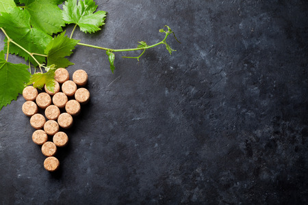 Wine corks grape shape and vine on stone table. Top view with copy space for text Reklamní fotografie