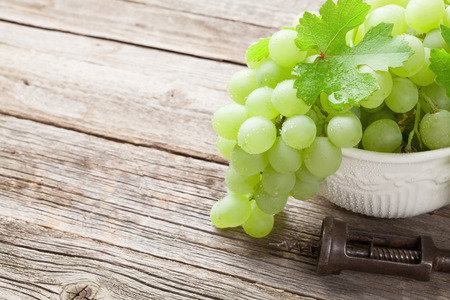 white grape: White grape in bowl on wooden table. View with copy space Stock Photo