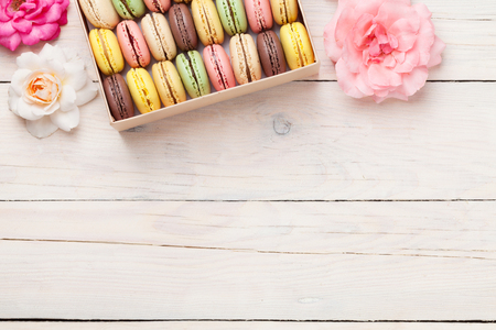 Colorful macaroons in a gift box on wooden table. Sweet macarons and flowers. Top view with copy space