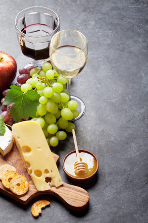 delicatessen: Red and white wine, grape, cheese and honey on stone table. View with copy space