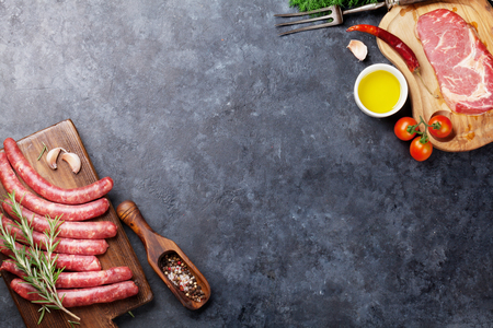 Sausages, meat and ingredients for cooking. Top view on stone table with copy space 写真素材