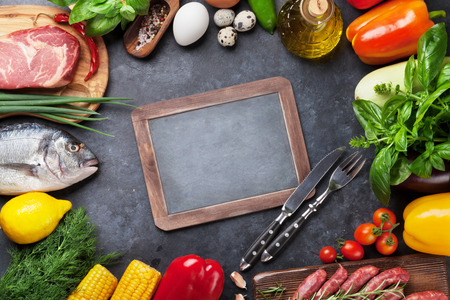 야채, 생선, 고기와 재료를 요리. 토마토, 가지, 옥수수, 쇠고기, 계란. 돌 테이블에 복사 공간 칠판 상위 뷰