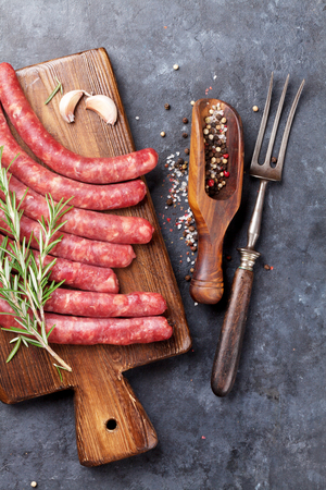 saucisse: Les saucisses crues et ingrédients pour la cuisson. Vue de dessus sur la table en pierre