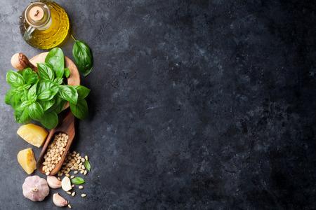 Pesto sugo di cottura. Basilico, olio d'oliva, parmigiano, aglio, pinoli. Vista superiore sul tavolo di pietra scura con copia spazio per il testo