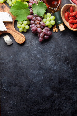 White wine, grape, sausages and cheese on stone table. Top view with copy space Stock Photo