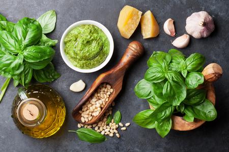 mortero: Pesto cocinar la salsa. Albahaca, aceite de oliva, queso parmesano, ajo, piñones. Vista superior de una mesa de piedra oscura Foto de archivo