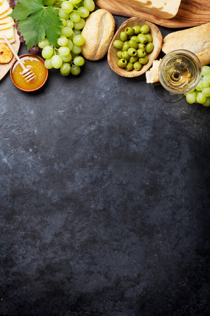 delicatessen: White wine, grape, bread, honey and cheese on stone table. Top view with copy space