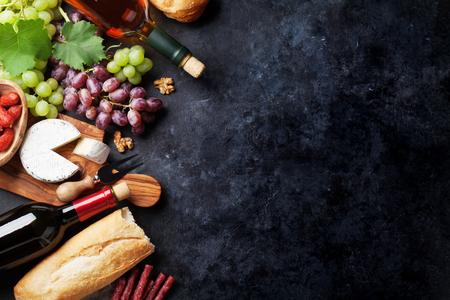 赤と白のワインのボトル、ブドウ、チーズとソーセージ石のテーブルの上です。コピー スペース平面図 写真素材