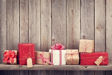 cajas navideñas: Christmas gift boxes in front of wooden wall with copy space. Retro toned