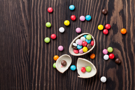 chocolate egg: Colorful candies and chocolate egg on wooden background. Top view with copy space Stock Photo