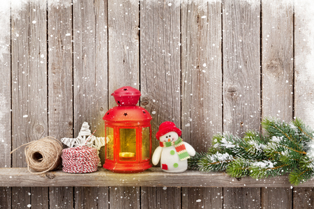 christmas tree decoration: Christmas candle lantern, tree and decor in front of wooden wall with copy space