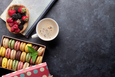 Colorful macaroons and berries on stone table. Sweet macarons and coffee cup. Top view with copy space Stock Photo