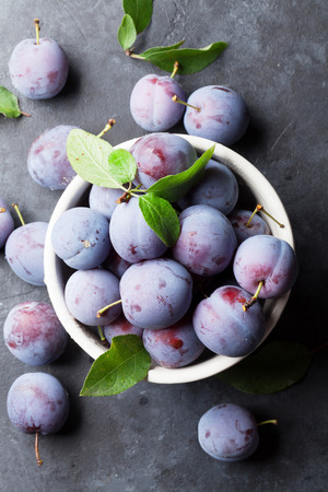 marble stone: Garden plums in bowl on stone table. Top view
