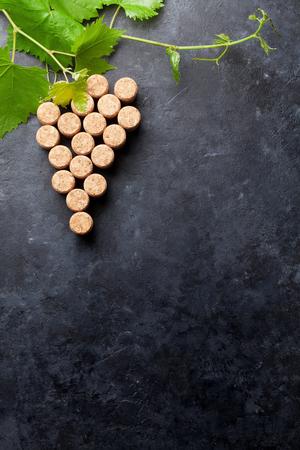 De wijn kurkt druivenvorm en wijnstok op steenlijst. Bovenaanzicht met kopie ruimte voor uw tekst Stockfoto