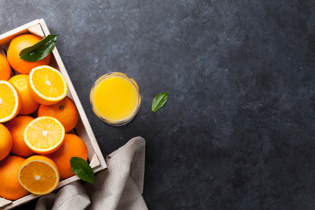 copies: Fresh orange fruits and juice on stone table. Top view with copy space