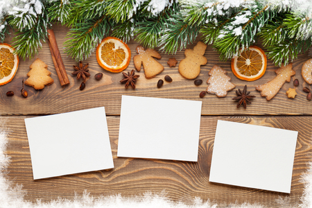 Christmas wooden background with photo frames, snow fir tree, spices and gingerbread cookies