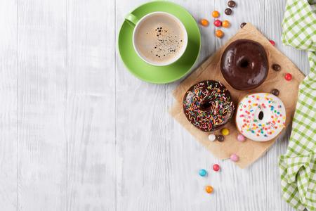 Donuts en koffie op houten tafel. Bovenaanzicht met een kopie ruimte