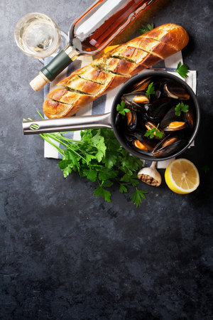 marble stone: Mussels in copper pot and white wine on stone table. Top view with copy space
