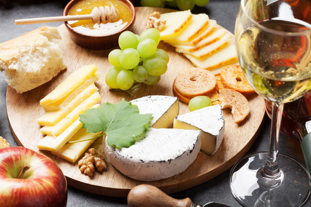 queso fresco blanco: Vino blanco, uva, pan, plato de queso y miel en la mesa de piedra