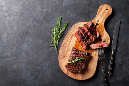 돌 테이블 위에 커팅 보드에 얇게 썬된 쇠고기 스테이크 구이. 복사 공간이있는 상위 뷰 스톡 콘텐츠