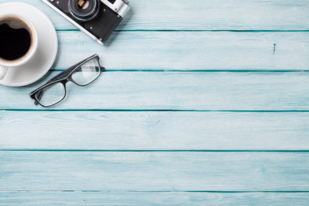 work table: Wooden table with camera, glasses and coffee. Top view with copy space. Stock Photo