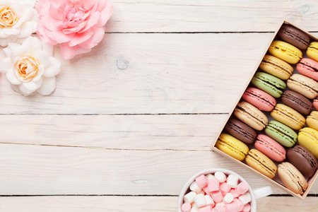 coffee and cake: Colorful macaroons and marshmallow on wooden table. Sweet macarons in gift box. Top view with copy space for text Stock Photo