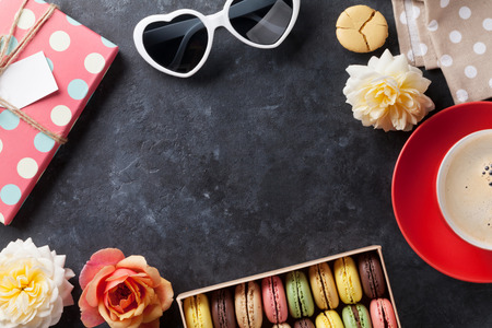 white stones: Colorful macaroons and coffee on stone table. Sweet macarons in gift box and flowers. Top view with copy space