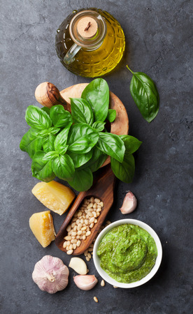 Pesto sauce cooking. Basil, olive oil, parmesan, garlic, pine nuts. Top view on dark stone table