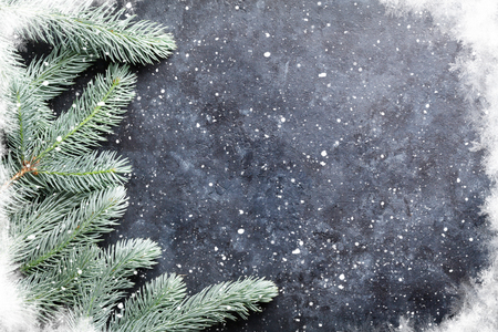 Christmas background with fir tree and snow. Over stone texture with copy space for text