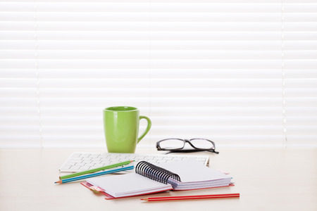 wood blinds: Office workplace with pc, charts and coffee cup on wood desk table in front of window with blinds Stock Photo