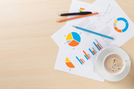 copyspace: Office desk workplace with coffee cup and charts on wooden table. Top view with copy space Stock Photo