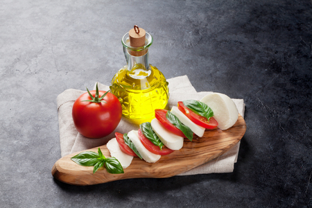 basil herb: Caprese salad. Mozzarella cheese, tomatoes and basil herb leaves on cutting board over stone table Stock Photo
