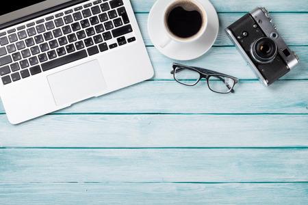 Bordtafel met laptop, koffie en camera op houten tafel. Workplace. Bovenaanzicht met kopie ruimte Stockfoto