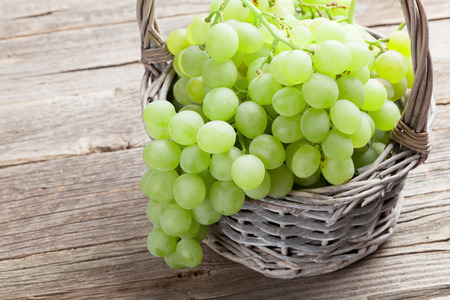 wooden basket: White grape in basket on wooden table