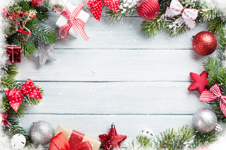 Christmas wooden background with snow fir tree and decoration. Top view with copy space for your text