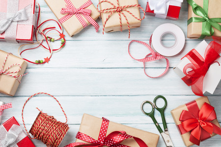 gift ribbon: Christmas background with gift boxes on wooden table. Top view with copy space. Gift wrapping Stock Photo