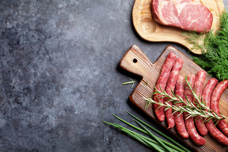 Sausages, meat and ingredients for cooking. Top view on stone table with copy space Фото со стока