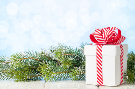 christmas gift box: Christmas gift box and fir tree branch on wooden table. View with copy space