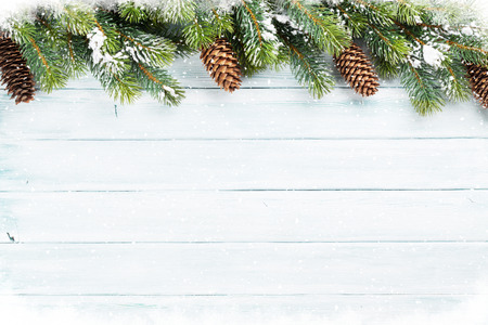 Christmas wooden background with snow fir tree. Top view with copy space for your text